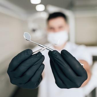 Nahaufnahme der chirurgischen ausrüstung gehalten mit handschuhen