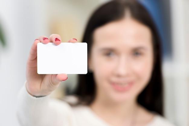 Nahaufnahme der defocus jungen geschäftsfrau, die weiße visitenkarte zeigt