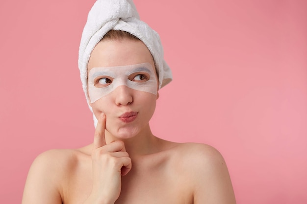 Nahaufnahme der denkenden jungen frau mit einem handtuch auf dem kopf nach dem duschen, schaut weg und berührt die wange, kann keine entscheidung treffen, steht auf.