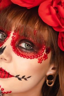 Nahaufnahme der details des dia de los muertos make-up eines schönen jungen mädchens.
