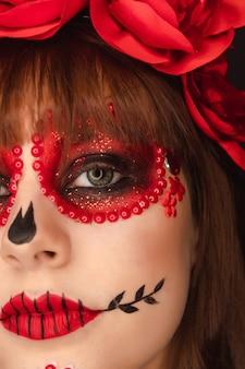 Nahaufnahme der details von dia de los muertos make-up eines jungen mädchens.