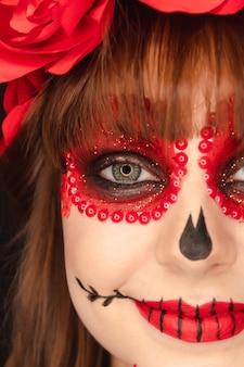 Nahaufnahme der details von dia de los muertos make-up eines schönen mädchens.