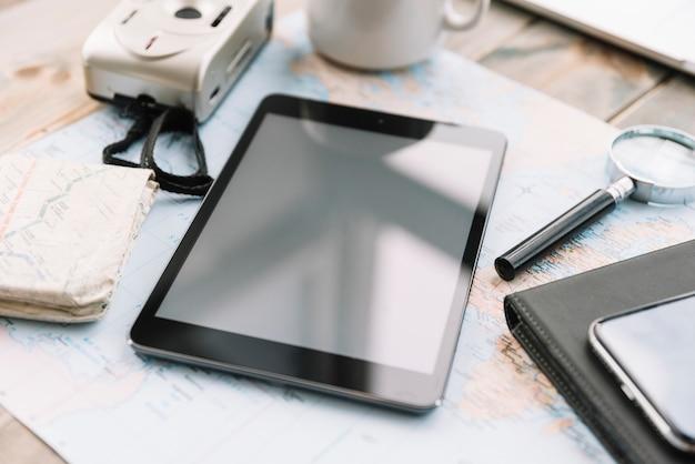 Nahaufnahme der digitalkamera; digitales tablett; lupe und tagebuch auf karte