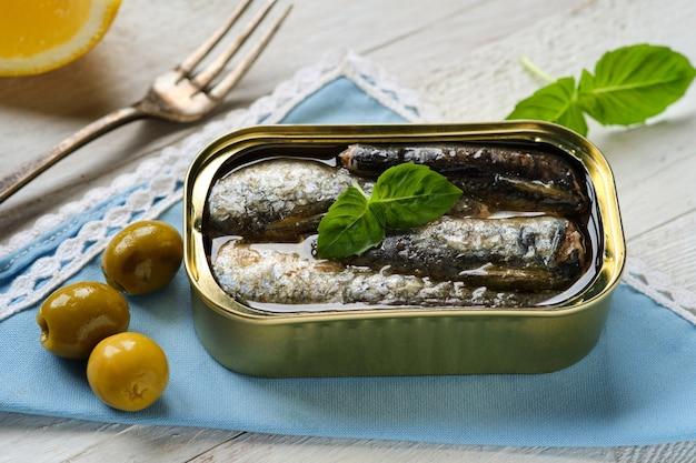 Nahaufnahme der dose sardinen in öl, mit einem basilikumblatt und oliven auf blauer serviette
