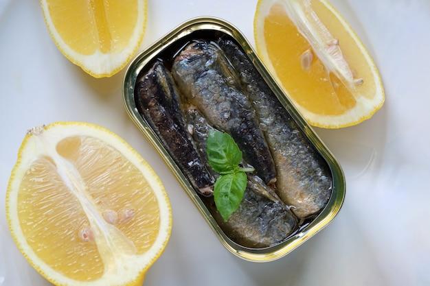 Nahaufnahme der dose sardinen in öl, mit einigen basilikumblättern und zitronenstücken