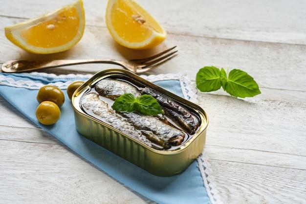 Nahaufnahme der dose sardinen in öl, mit etwas basilikum und olivenblättern auf blauer serviette und kopierraum