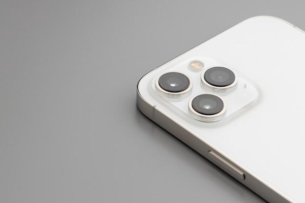 Nahaufnahme der dreifachlinsenkamera des modernen smartphones auf grau