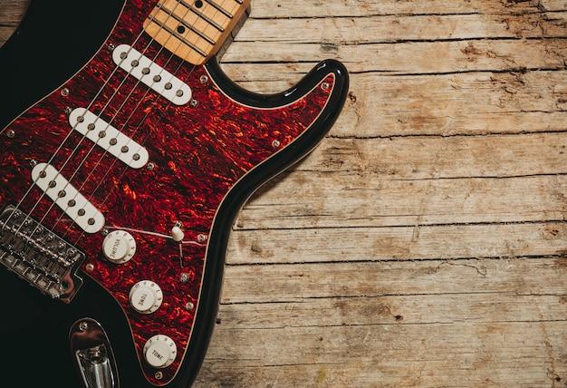 Nahaufnahme der e-gitarre liegend auf hölzernem hintergrund der weinlese, mit kopienraum