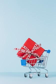 Nahaufnahme der eingewickelten roten geschenkbox im einkaufswagen auf blauem hintergrund