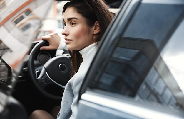 Nahaufnahme der eleganten geschäftsfrau, die im auto zur arbeit kommt