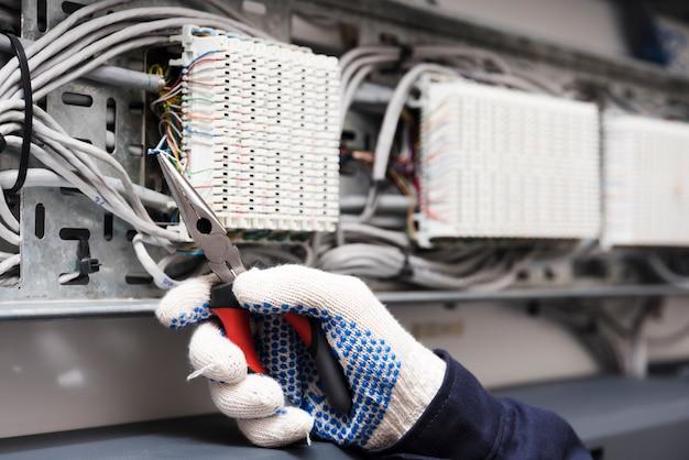 Nahaufnahme der elektrikerhand, die elektrischen kabeldraht mit einer zange schneidet