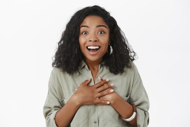 Nahaufnahme der entzückten amüsierten und glücklichen jungen charmanten afroamerikanerfrau mit lockigem haarschnitt, der handflächen auf brust mit dankbarer geste hält