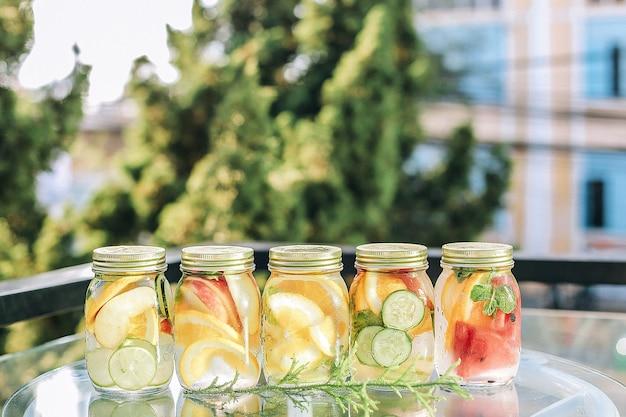 Nahaufnahme der erfrischenden getränke mit früchten in einem glas auf dem tisch unter dem sonnenlicht