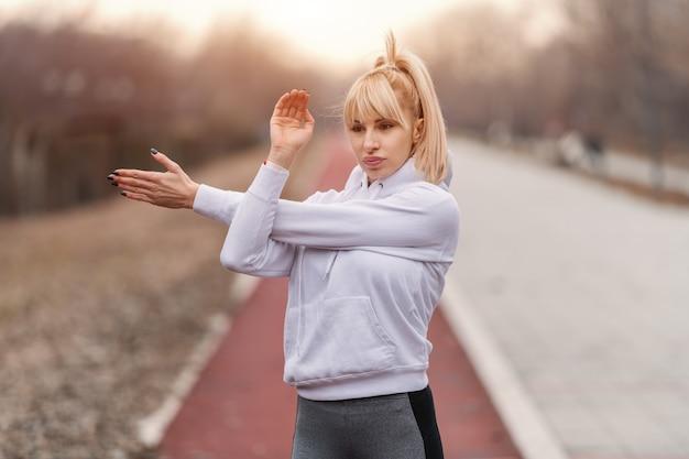 Nahaufnahme der ernsthaften herrlichen blonden kaukasischen frau in sportbekleidung und mit pferdeschwanz, der arme vor dem laufen streckt.