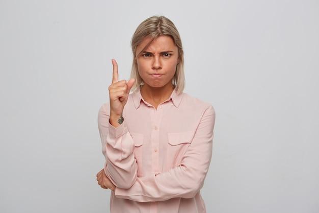 Nahaufnahme der ernsthaften strengen blonden jungen frau trägt rosa hemd sieht gestresst aus und zeigt mit finger lokalisiert über weiße wand