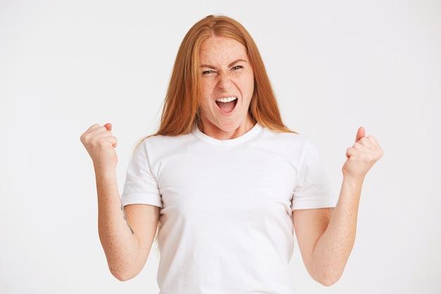 Nahaufnahme der erstaunten reizenden jungen frau mit langen roten haaren und sommersprossen trägt t-shirt