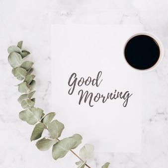 Nahaufnahme der eukalyptusniederlassung mit text des guten morgens auf papier und kaffeetasse über strukturiertem hintergrund des marmors