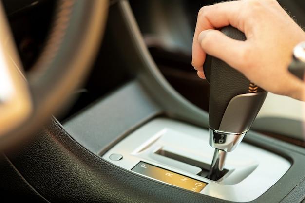 Nahaufnahme der fahrerin, die ihre hand am automatischen schalthebel hält, der als auto fährt.