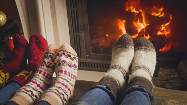Nahaufnahme der familie mit kind in wollsocken, die sich durch das brennende feuer erwärmen
