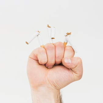 Nahaufnahme der faust die zigarettenkippen lokalisiert auf weißem hintergrund faltend