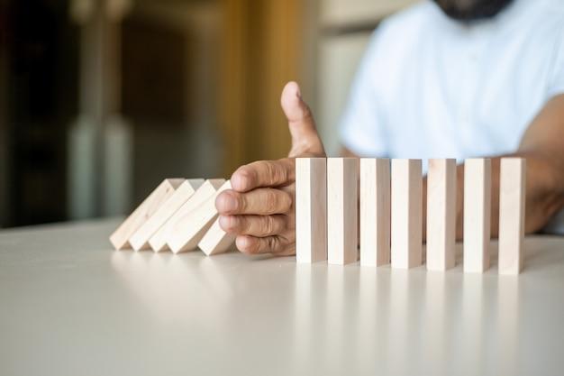 Nahaufnahme der fingergeschäftsfrau, die verhindert, dass der holzblock in die dominolinie fällt, mit investment insurance alternative und preven, business risk control-konzept.