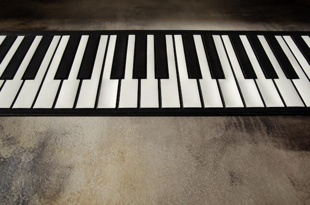 Nahaufnahme der flachen klaviertastatur, ansicht von oben. klaviertasten auf strukturiertem betonhintergrund.