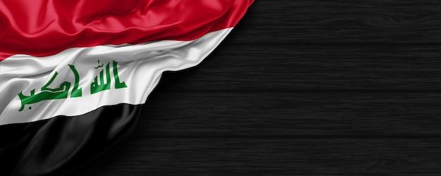 Nahaufnahme der flagge der vereinigten staaten des irak auf dem schwarzen holzhintergrund 3d-rende
