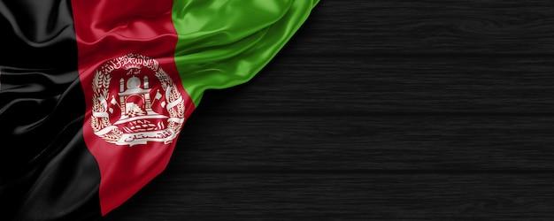 Nahaufnahme der flagge der vereinigten staaten von afghanistan auf dem schwarzen holzhintergrund 3d-rendering