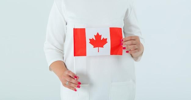 Nahaufnahme der flagge von kanada in den weiblichen händen.