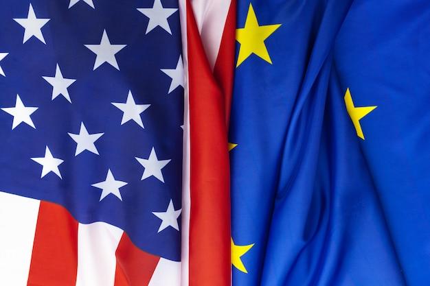 Nahaufnahme der flaggen der usa und der europäischen union, die zusammen auf tisch liegen