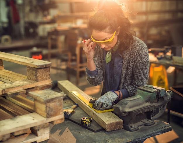 Nahaufnahme der fleißigen fokussierten professionellen ernsthaften zimmermannsfrau, die mit einem lineal arbeitet und markierungen auf dem holz am tisch in der stoffwerkstatt macht.