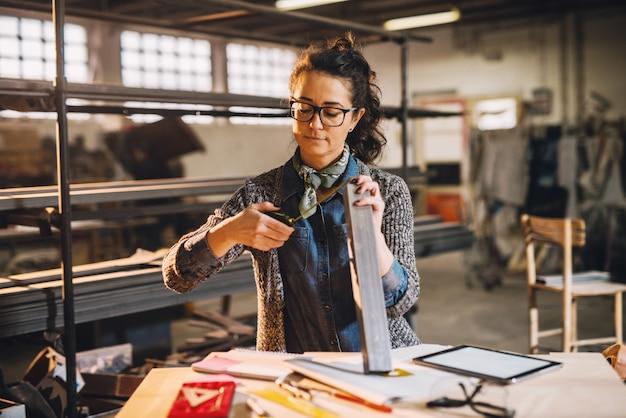 Nahaufnahme der fleißigen fokussierten professionellen motivierten geschäftsfrau, die metallrohr mit einem maßband in der sonnigen stoffwerkstatt misst.