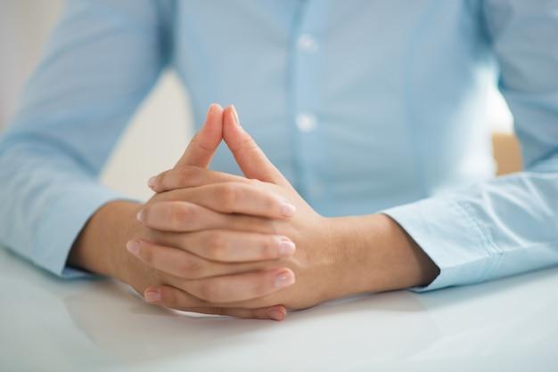 Nahaufnahme der frau bei tisch sitzend mit ihren händen umklammert