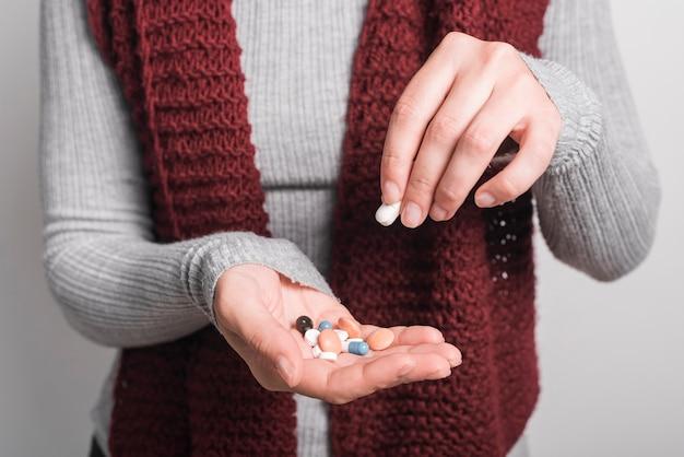Nahaufnahme der frau bunte pillen anhalten