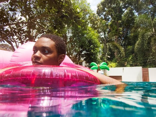 Nahaufnahme der frau der afrikanischen abstammung, die in das pool schwimmt