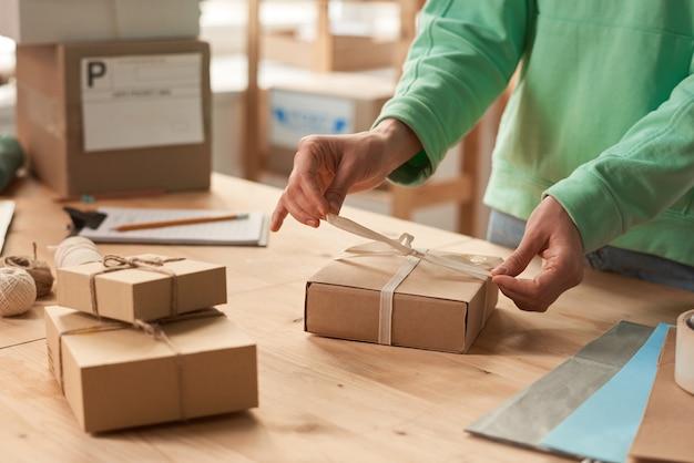 Nahaufnahme der frau, die am tisch steht und geschenkboxen mit bändern zum urlaub verziert