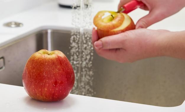 Nahaufnahme der frau, die apfel über spüle in der küche schält