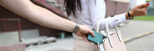 Nahaufnahme der frau, die auf straße geht. mann stehlen smartphone von frauentasche.