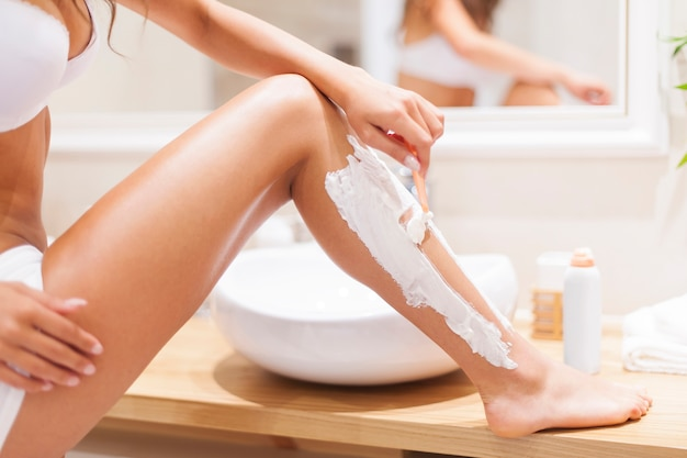 Nahaufnahme der frau, die beine im badezimmer rasiert