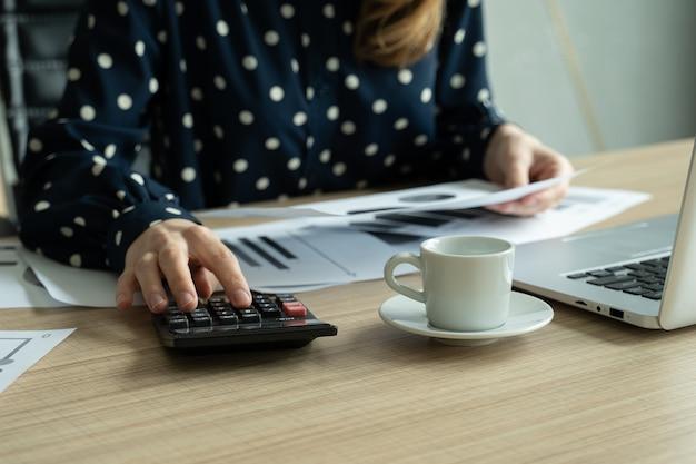 Nahaufnahme der frau, die das budget mit taschenrechner und laptop plant, die dokumente am schreibtisch lesen?