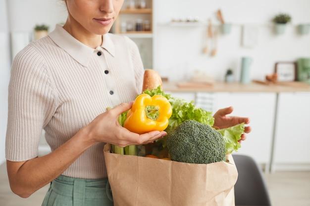 Nahaufnahme der frau, die das frische gemüse aus der papiertüte zu hause herausnimmt