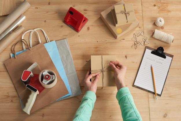 Nahaufnahme der frau, die das geschenk in den karton packt und es mit band am tisch bindet