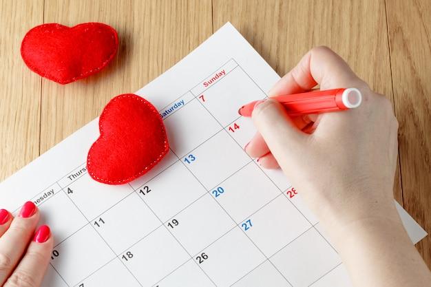 Nahaufnahme der frau, die datum auf kalender hervorhebt