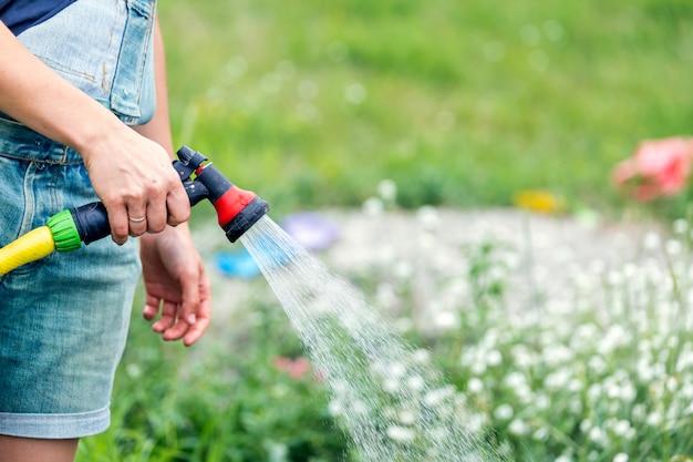 Nahaufnahme der frau, die die pflanzen im garten wässert
