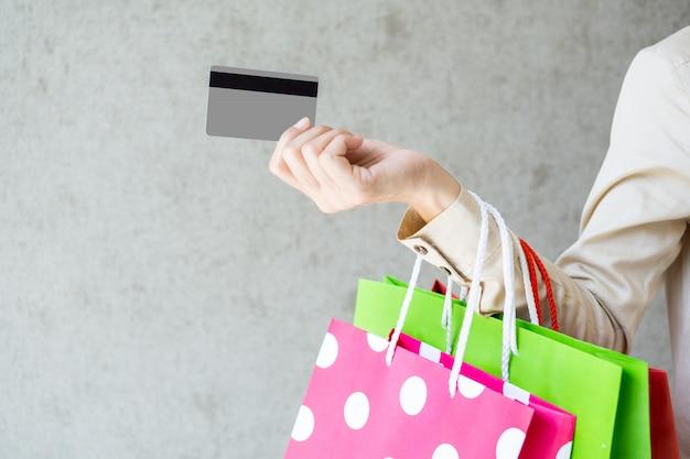 Nahaufnahme der frau, die einkaufstaschen hält und eine kreditkarte verwendet.