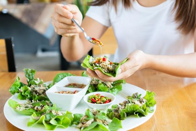 Nahaufnahme der frau, die gebratenen makrelen-würzigen salat isst, der mit frischem gemüse, chilischoten, erdnuss und thailändischer würziger fischsauce serviert wird. dieses essen ist ein traditionelles thailändisches menü namens maing-pla-too. nahansicht