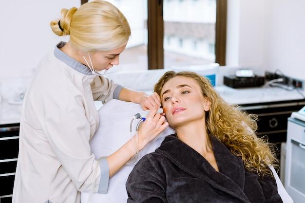 Nahaufnahme der frau, die gesichts-hydro-mikrodermabrasions-peeling-behandlung und junge ärztin kosmetikerin an der schönheitsklinik erhält. hydra staubsauger.