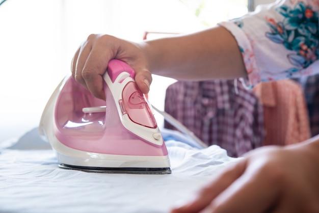 Nahaufnahme der frau, die kleidung auf bügelbrett bügelt