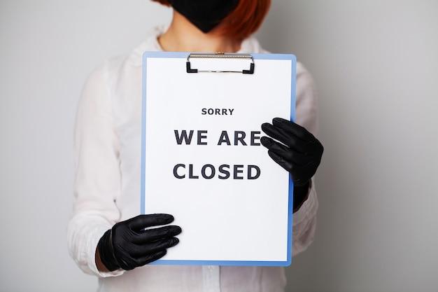 Nahaufnahme der frau, die leer mit inschrift hält, wir sind geschlossen und fordern die verbreitung von covid-19 auf.