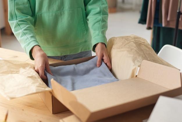 Nahaufnahme der frau, die neue kleidung in die schachtel packt, die sie ein paket für lieferung macht